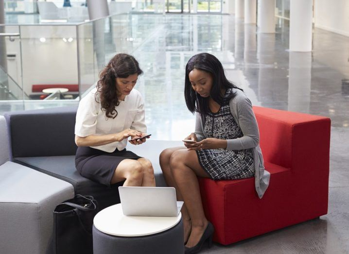 Two woman in business attire next to each other looking at their phones.