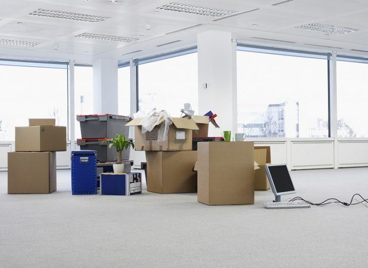 Stack of boxes and office equipment in the middle of an empty office.