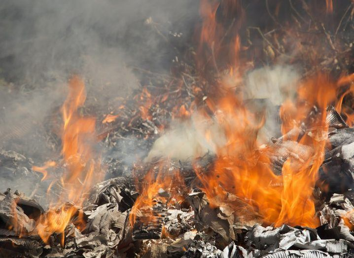 Image of burning wood, paper and other materials, with flames and smoke coming out of them.