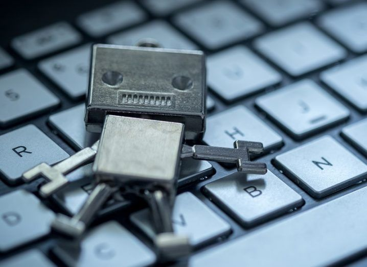 Small, boxy metal robot lying on a keyboard.