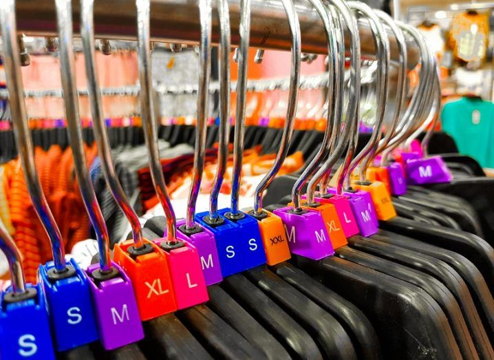 A rack of clothes hangers with different-coloured size tags.