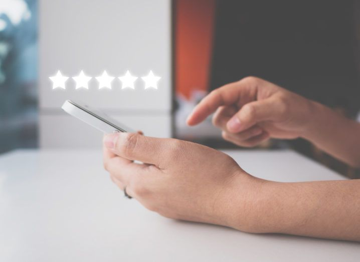 A woman using a smartphone to leave a five-star review of an online business.