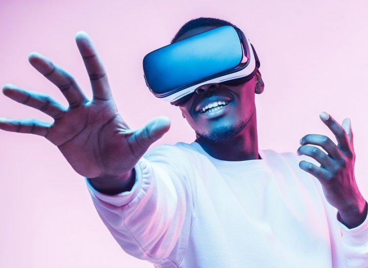 Man wearing a VR headset in a white jumper holding his hands out to touch something.