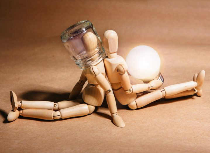 Two wooden figures are seated back to back. One holds a glowing lightbulb, the other has its head covered by a glass jar.