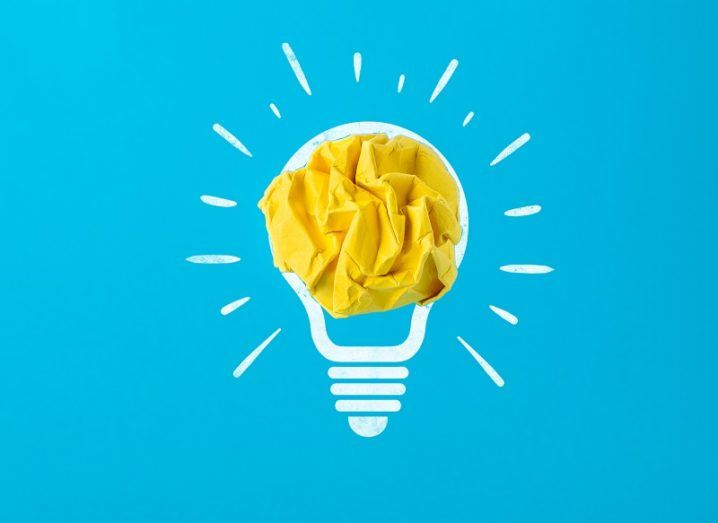 Abstract image of yellow crumpled paper in a white drawing of a lightbulb against a blue background.