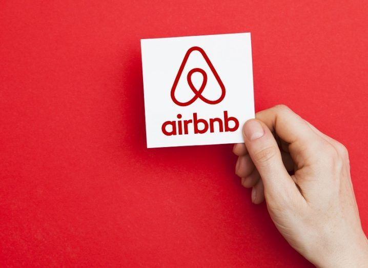 Hand holding a card with the Airbnb logo against a red background.