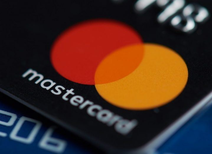 Close-up of the Mastercard logo on a black credit card.