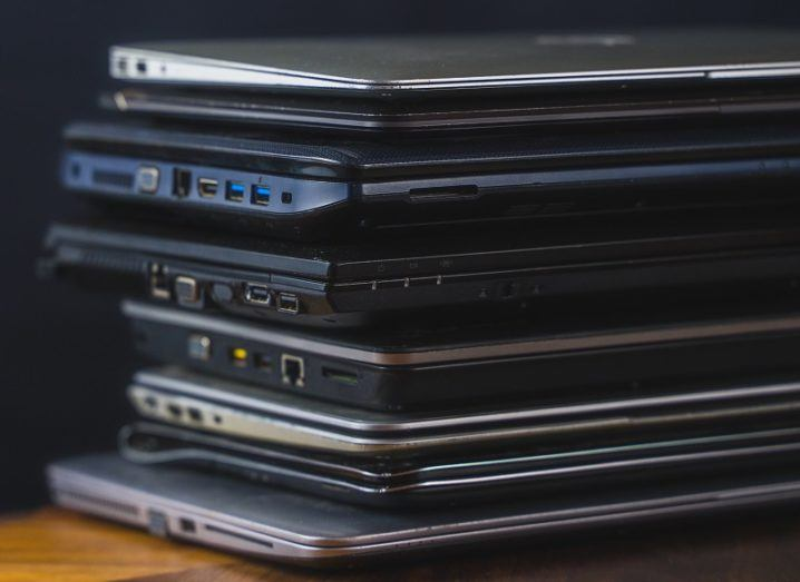 Stack of old laptops on a wooden table against a black background.