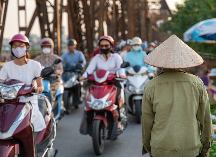 Vietnamese street full of people on mopeds wearing face masks.
