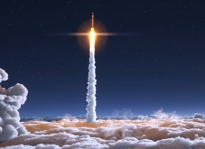 Rocket travelling into orbit through the clouds at great speed.