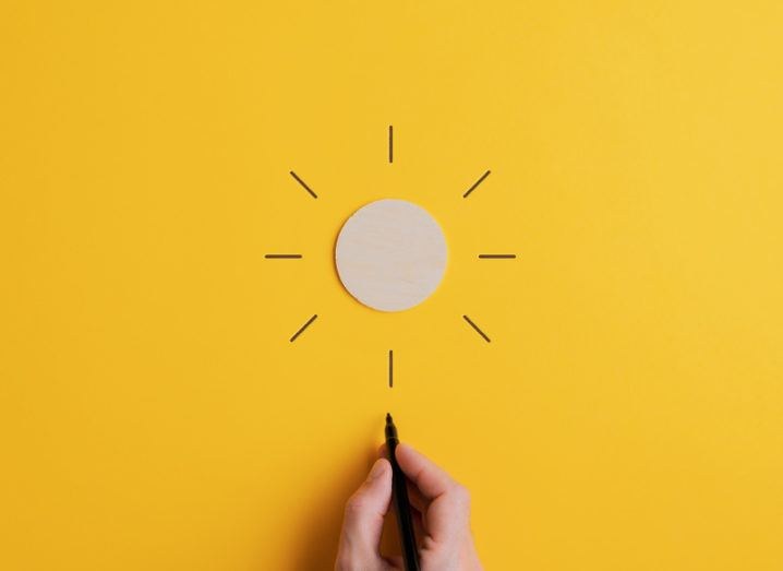 A white circle of card on a yellow background. A hand draws lines emanating out from the disc so that it looks like a sun shining.