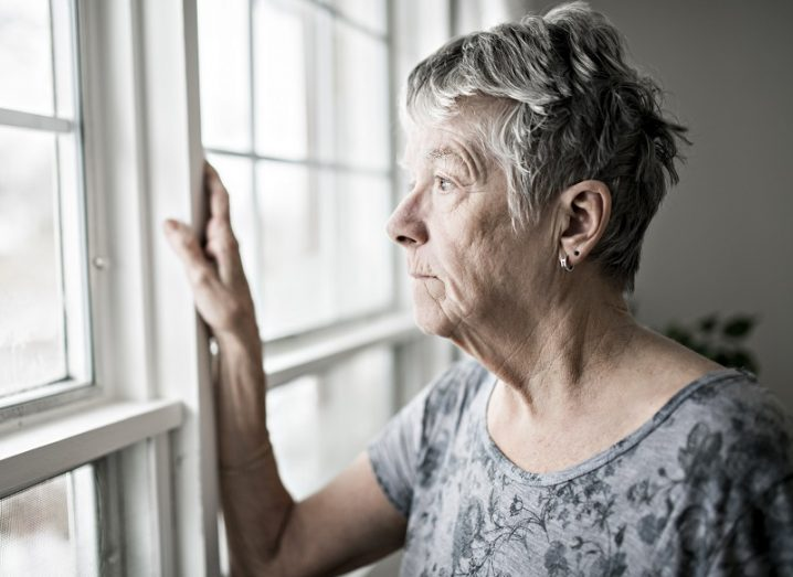 Elderly woman looking out of her window.