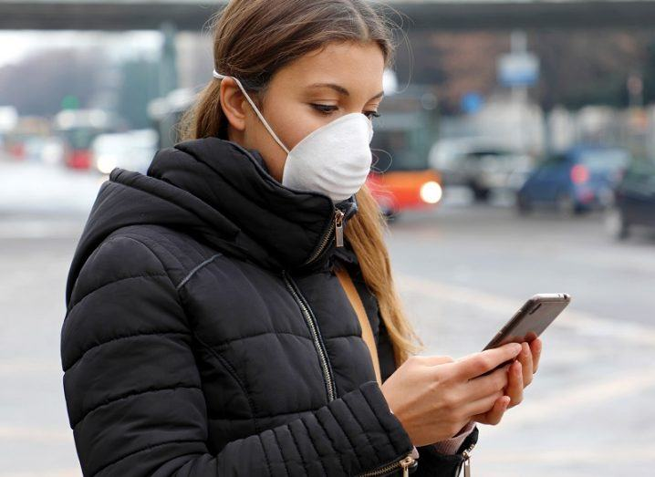 Woman wearing a face mask and looking at her phone on a street.