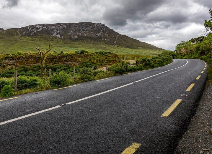 Empty road turning a bend in the Irish countryside.