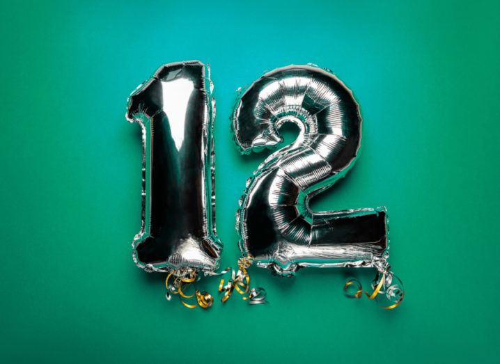 Silver foil balloons in the shape of the number 12 against a deep green background.