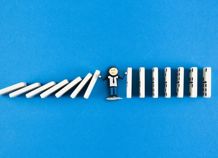 A small figure of a man amid a line of dominoes, preventing those falling on the right from knocking over the ones on his left.
