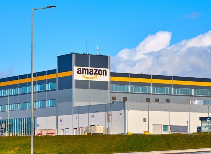 Amazon warehouse against a blue sky background with clouds.