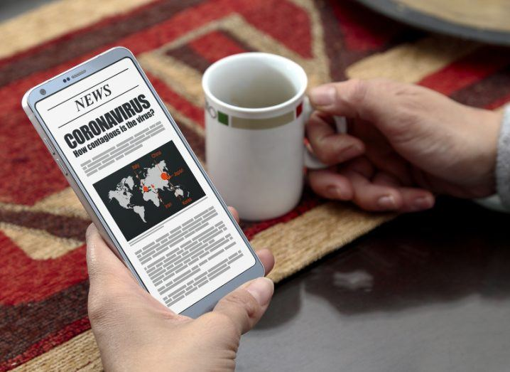 A woman holds a smartphone in one hand to read a news story about coronavirus while drinking a cup of coffee.