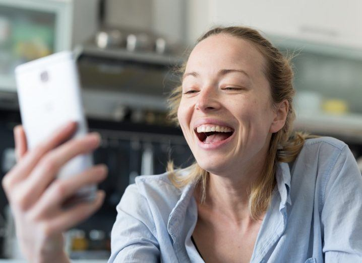 Woman in a blue shirt laughing during a video call on her phone in a kitchen.