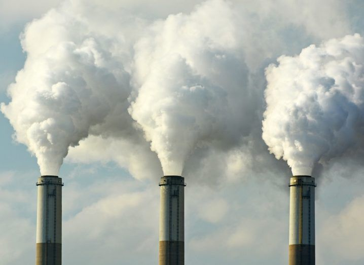Three chimneys at a power plant releasing large amounts of CO2 emissions.