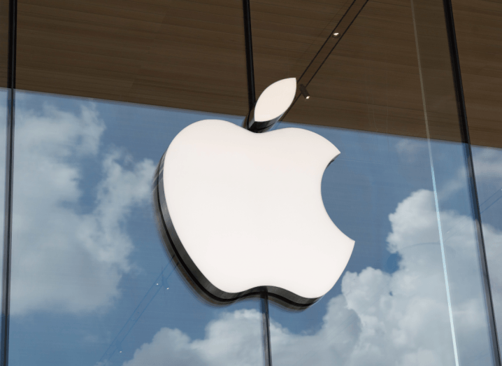 The Apple logo displayed on a glass wall.