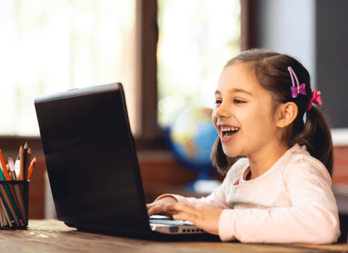 A child with pigtails in her hair, wearing a pink cardigan, uses a laptop.