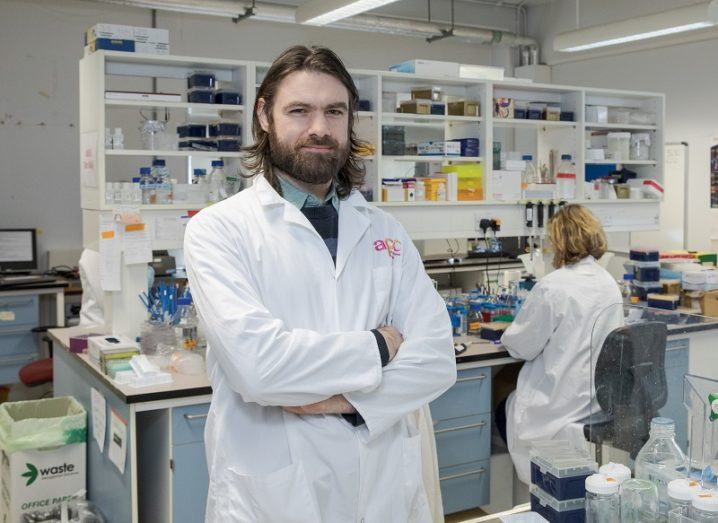 Dr Ciaran Lee crossing his arms in a white jacket with a lab and colleague behind him.