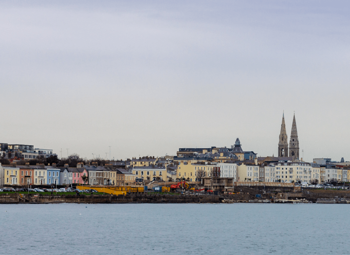 A stretch of colourful houses in front of a body of water, with a church spire in the background.