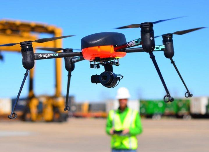 The black and orange Draganfly pandemic drone being operated at a dock by a man in a high-vis vest.