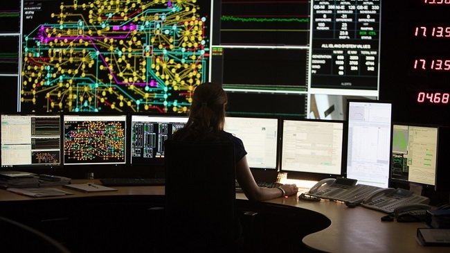 Simulation of EirGrid's national grid control centre with a person monitoring multiple screens.