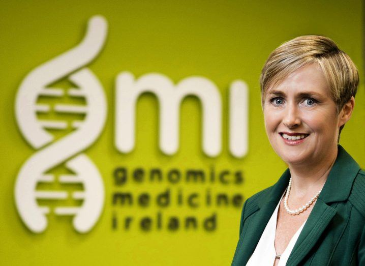 Dr Anne Jones of Genomics Medicine Ireland is standing in front of a green wall with GMI branding on it.