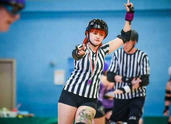 Helen Horkan in a black and white striped shirt playing rollerderby.