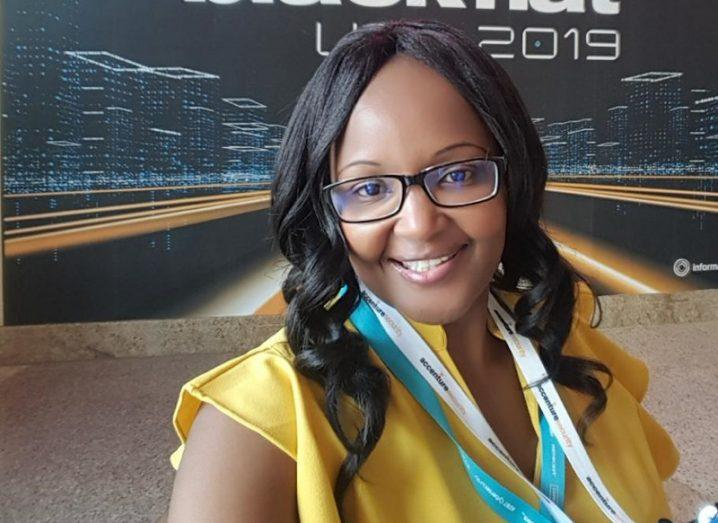 A head and shoulders photo of Noureen Njoroge, a smiling woman with long black hair, wearing glasses and a yellow blouse.
