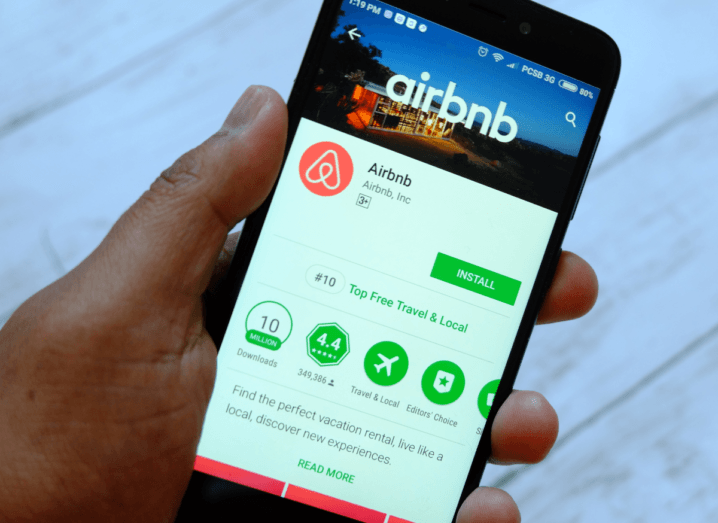 A person holding an Android phone displaying the Airbnb app on the Google Play store.