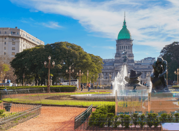 A plaza under a sunny sky with statues and fountains in front of an old grey government building.