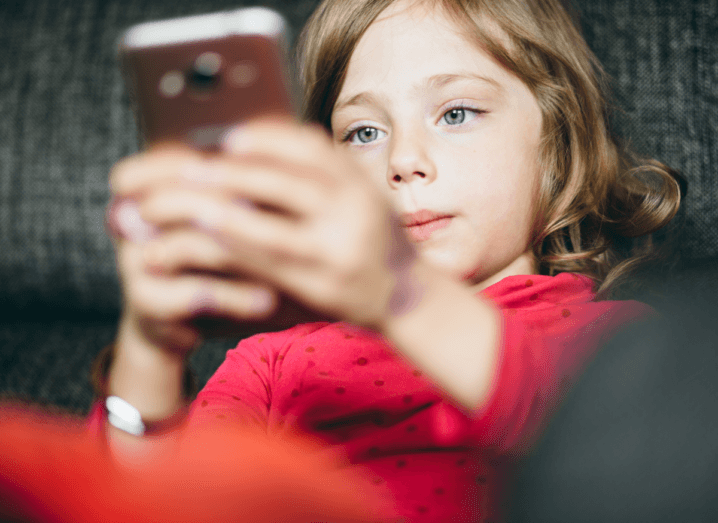 A child wearing a red jumper plays with a phone on a sofa.