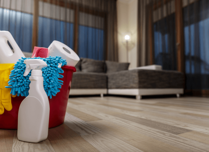 Cleaning equipment in a red bucket on the floor of a modern apartment.