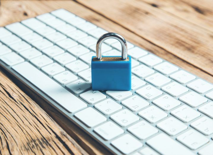A small blue padlock sitting on a white keyboard on a wooden surface, representing protection against cyberattacks.