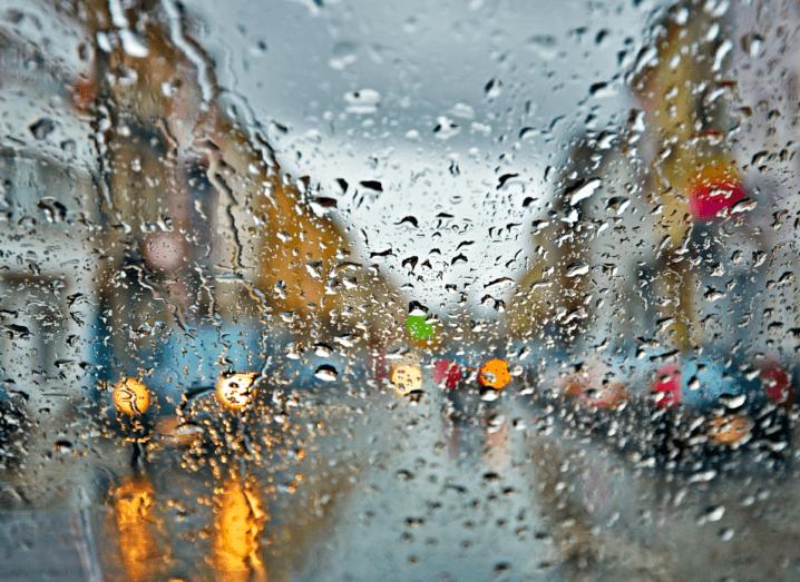 Rain on the windscreen of a car driving through a city.