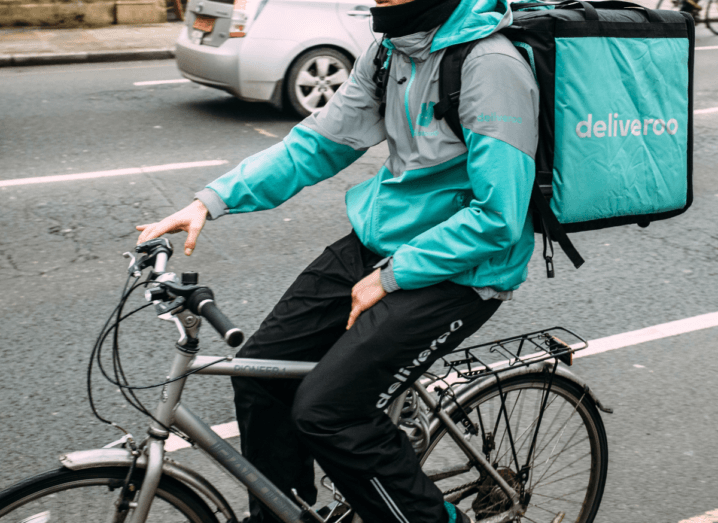 A cyclist wearing deliveroo gear and a large bag for delivering food, while cycling down a busy street.