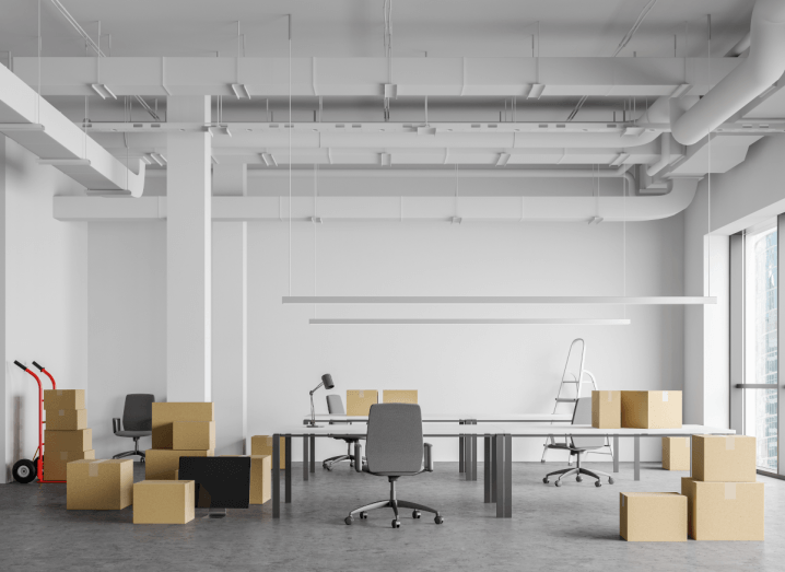 An empty office with cardboard boxes piled up around the desks and chairs as the previous occupants plan to move out.