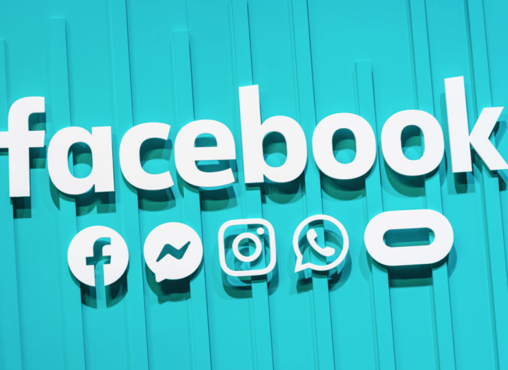 The Facebook logo displayed on a blue wall, beside logos for Facebook's other brands, which includes Messenger, WhatsApp, Instagram and Oculus.
