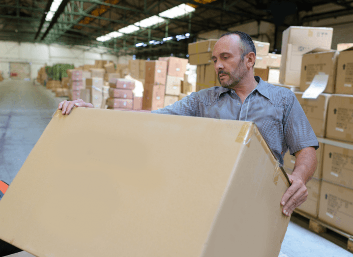 A man in a grey shirt loading a cardboard box onto a platform in front of lots of other cardboard boxes.