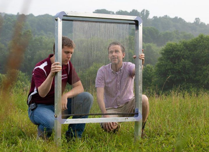 Jonathan Boreyko and Brook Kennedy inspecting a fog harp in a field.
