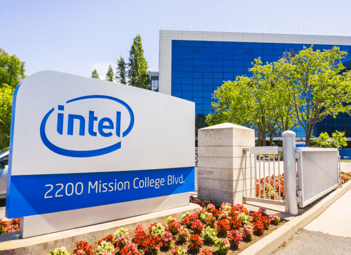 The Intel logo displayed on a sign outside an office building in Silicon Valley. The sky is blue and there are trees in the background.