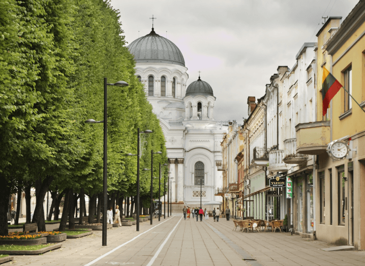 A white building at the end of an avenue of trees and a row of shops and cafes.