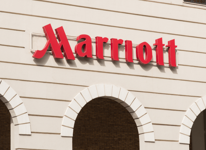 The red Marriott hotel logo on a white, panelled wall over arches.