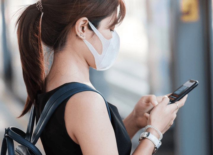 A woman wearing a mask using an iPhone X.