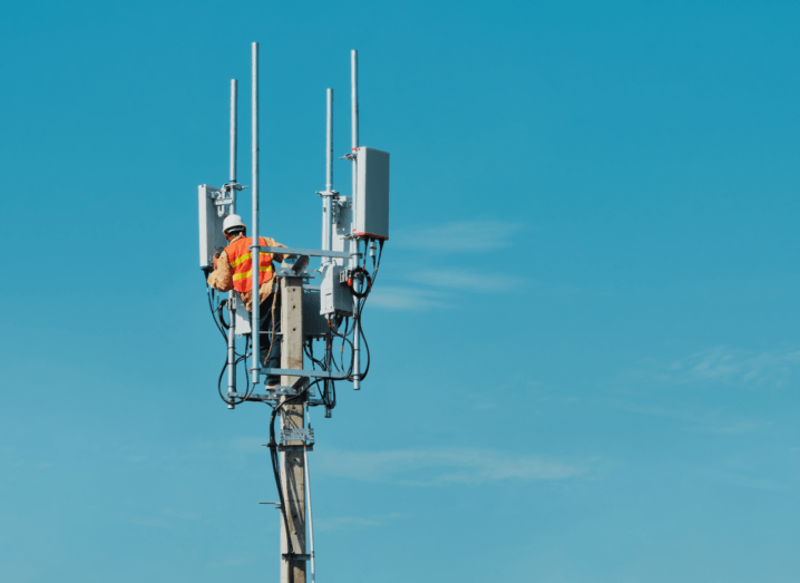 A phone mast or 5G infrastructure in front of a blue sky, with a technician standing on it wearing an illuminous orange jacket and white helmet.