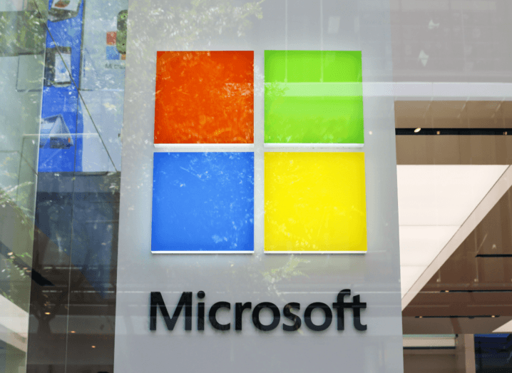 The Microsoft logo behind a pane of glass, with reflections of leaves on the outside.
